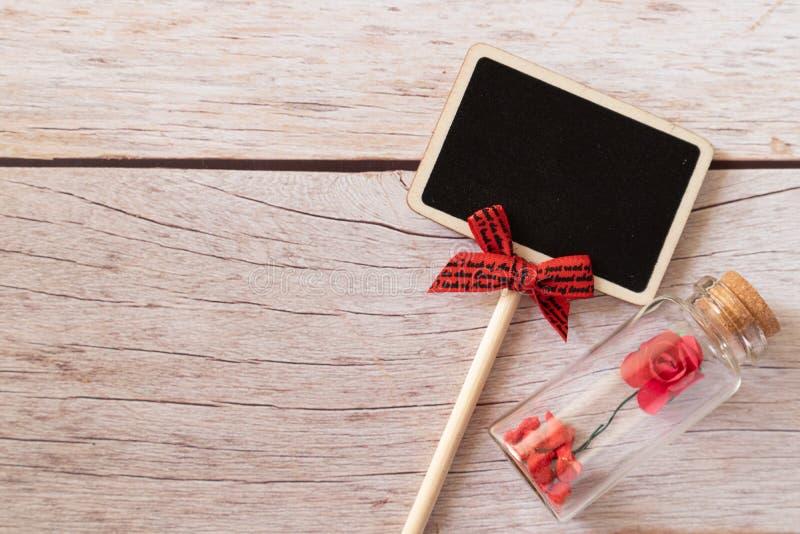 有红色玫瑰的黑标志棍子在微小的玻璃瓶 最小和简单的爱照片概念 免版税图库摄影