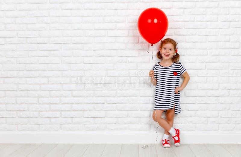 有红色球的愉快的滑稽的儿童女孩在砖墙附近 免版税库存图片
