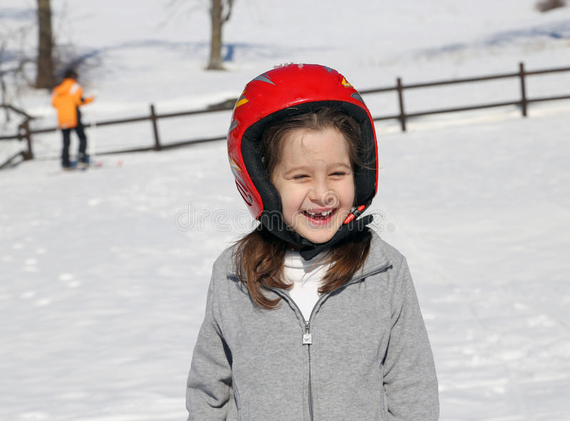 有红色盔甲的愉快的女孩在雪在冬天 库存照片