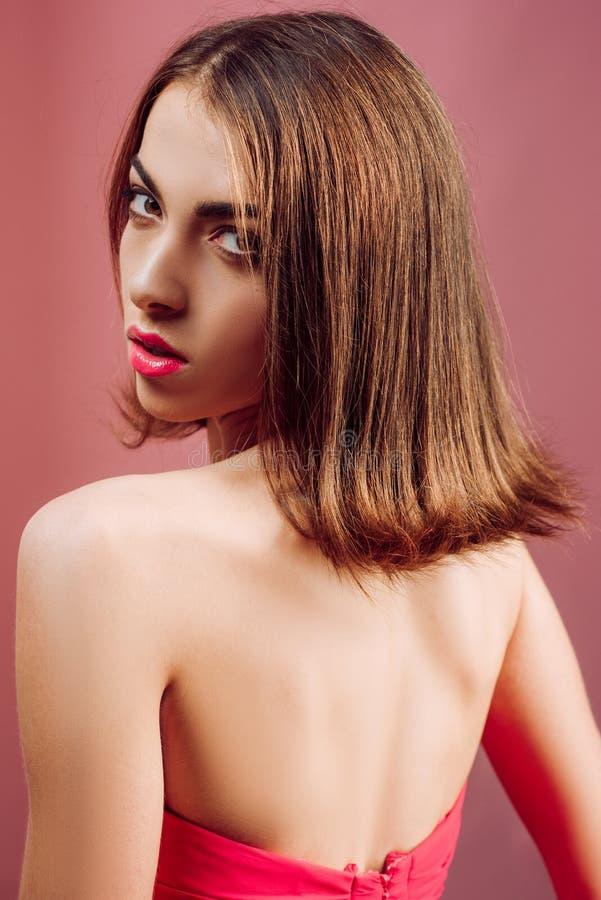 有红色礼服和红色嘴唇的秀丽妇女 发型称呼 时尚,秀丽,化妆用品 完善的皮肤 E 免版税库存图片