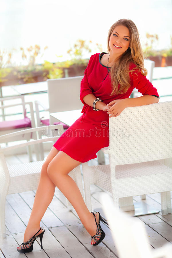 有红色礼服和金发摆在的美丽的性感的妇女室外 塑造女孩 库存照片