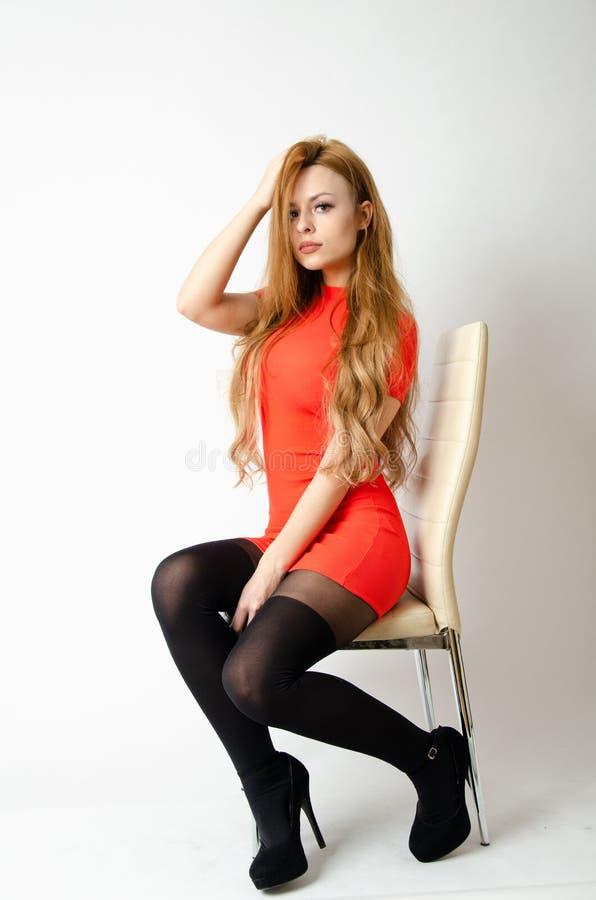 有红色礼服的女孩坐椅子 免版税库存照片