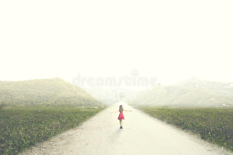 有红色礼服的妇女走到无限在自然中间 免版税库存照片