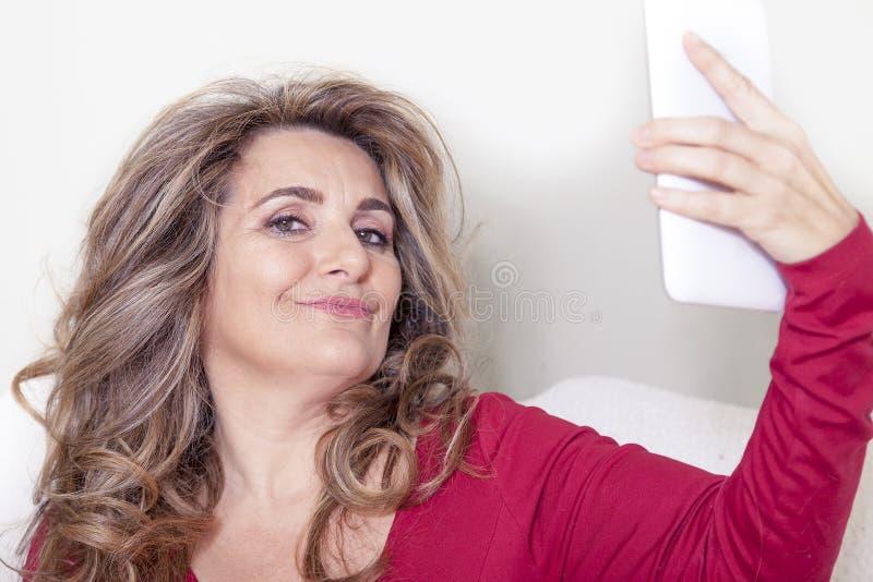 有红色礼服的美丽的夫人采取selfie 免版税库存图片
