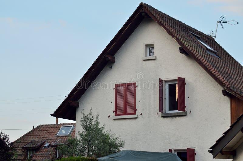 有红色窗口的房子 库存照片