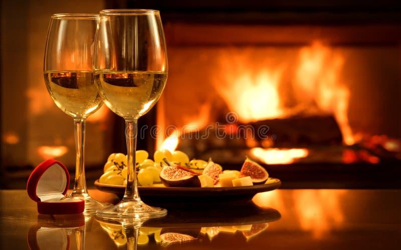 有红色箱子的两个酒葡萄酒杯有在壁炉背景的定婚戒指的 免版税库存照片