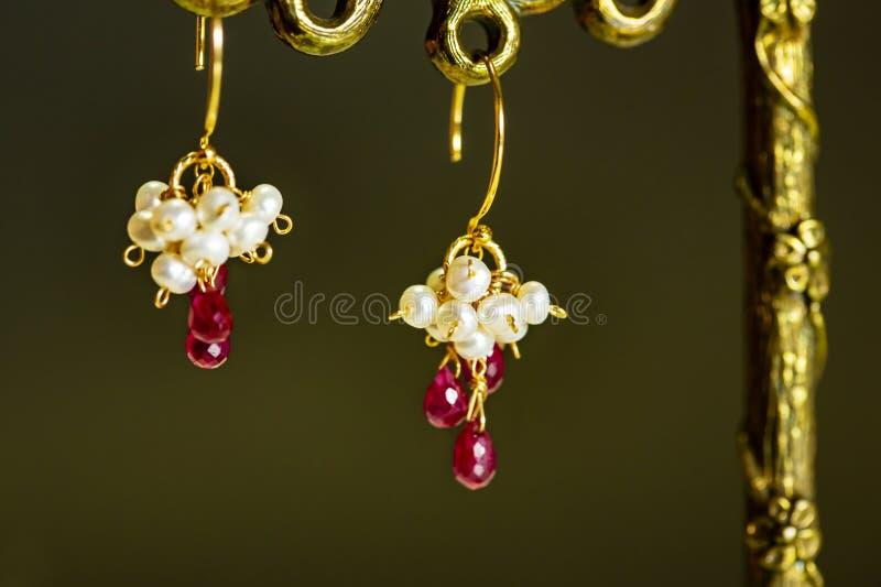 有红色红宝石的金黄耳环与在黑背景的白色珍珠 库存图片