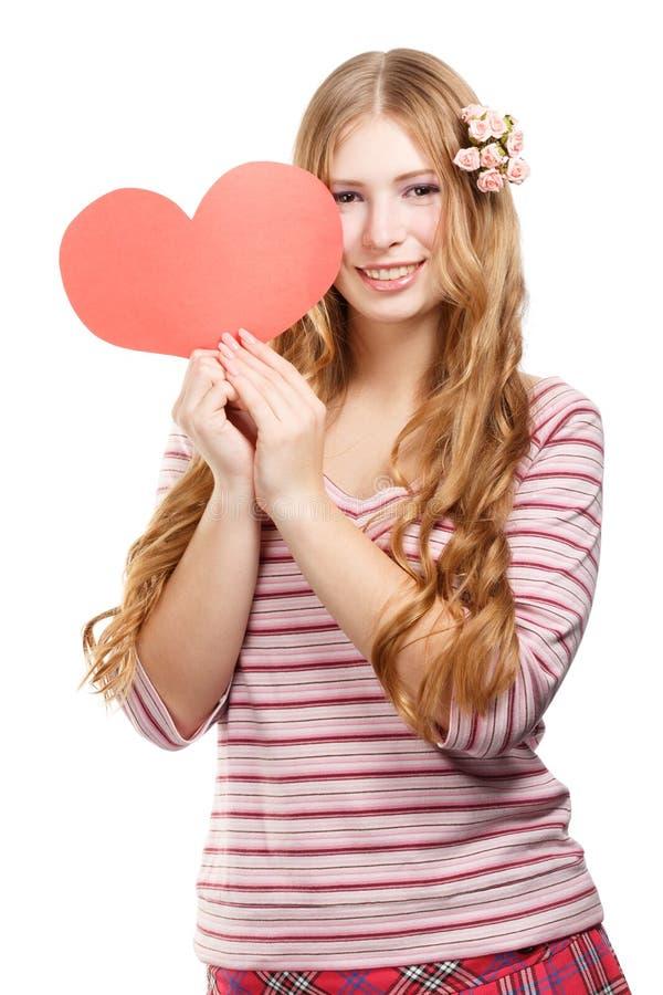 有红色纸华伦泰心脏的美丽的年轻微笑的妇女 免版税图库摄影