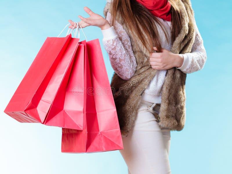 有红色纸购物袋的冬天妇女 免版税库存图片