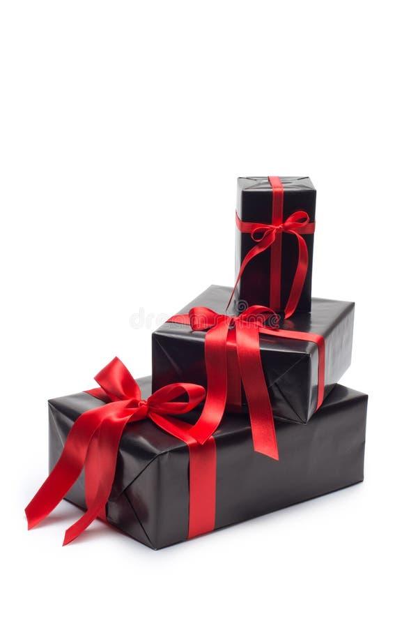 有红色缎丝带和弓的黑礼物盒 库存图片