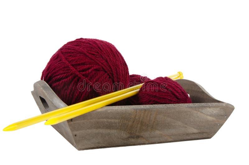 有红色编织的羊毛和针的木盘子 库存图片