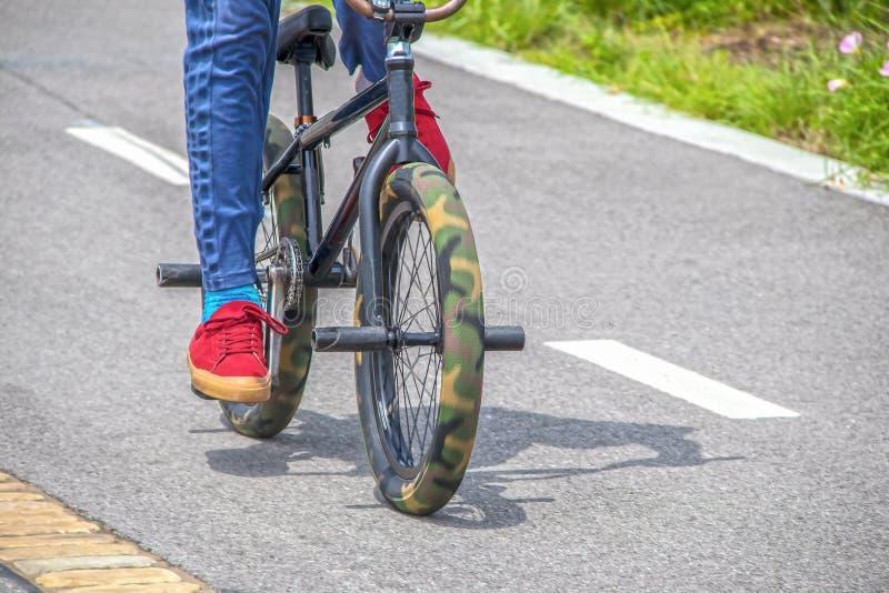 有红色网球鞋和蓝色牛仔裤的人乘坐的伪装肥胖轮胎和钉的微型把戏特技自行车在铺面 库存图片
