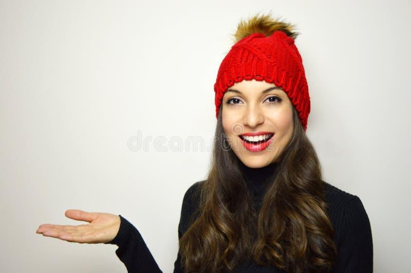 有红色羊毛帽子的微笑的女孩和红色唇膏显示您的在她的手上的产品在白色背景 复制空间 库存照片