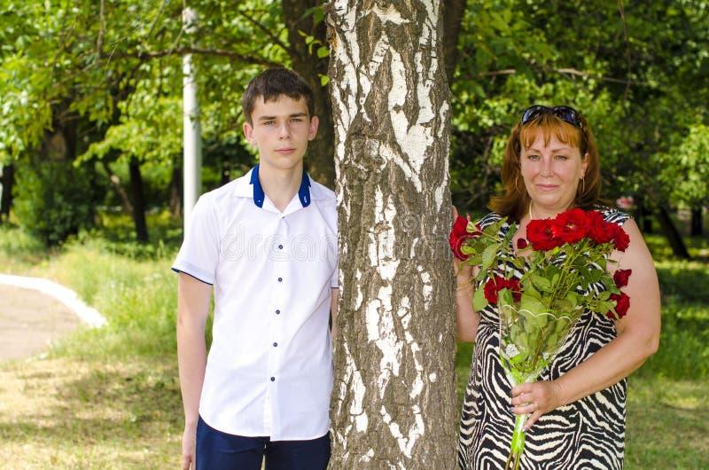 有红色花花束的妈妈和儿子在桦树附近站立 库存照片