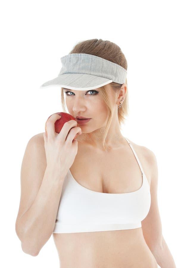 美丽的诱人的女性网球员用红色苹果。 图库摄影