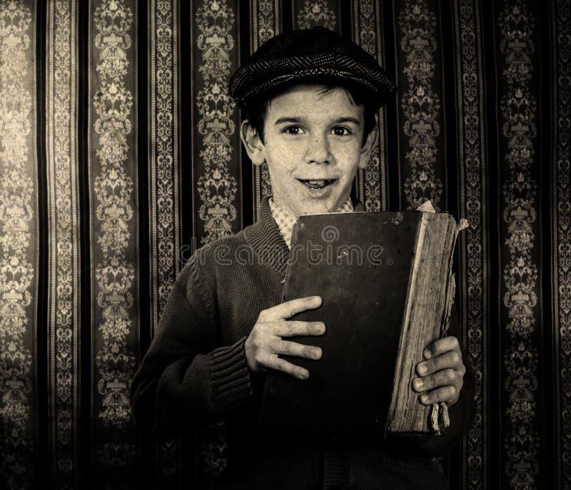 有红色葡萄酒书的孩子 库存照片