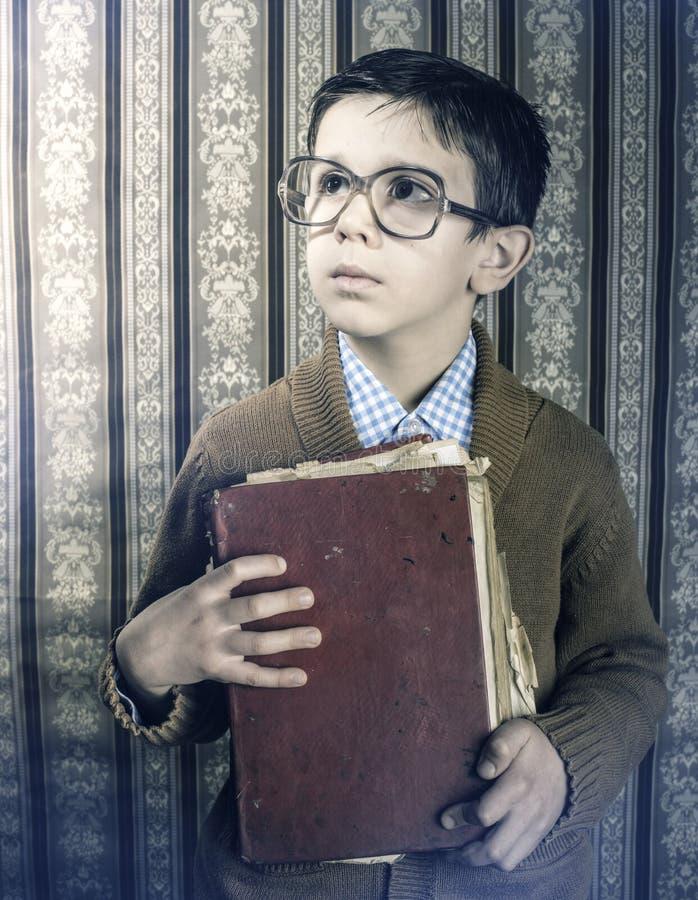 有红色葡萄酒书的孩子 免版税库存照片