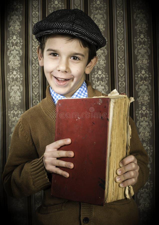 有红色葡萄酒书的孩子 免版税库存图片