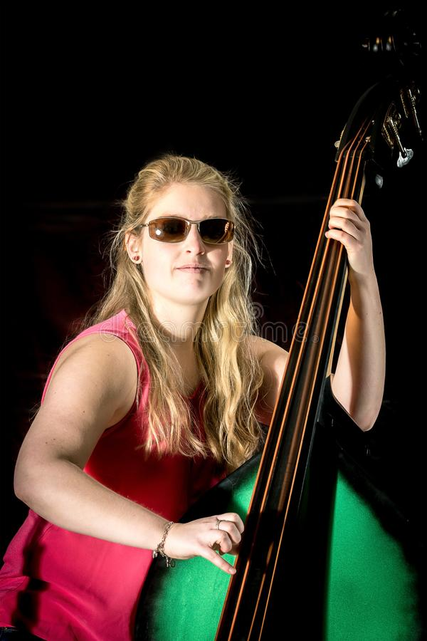 有红色衬衣的女性音乐家在一个低音提琴使用 免版税库存图片