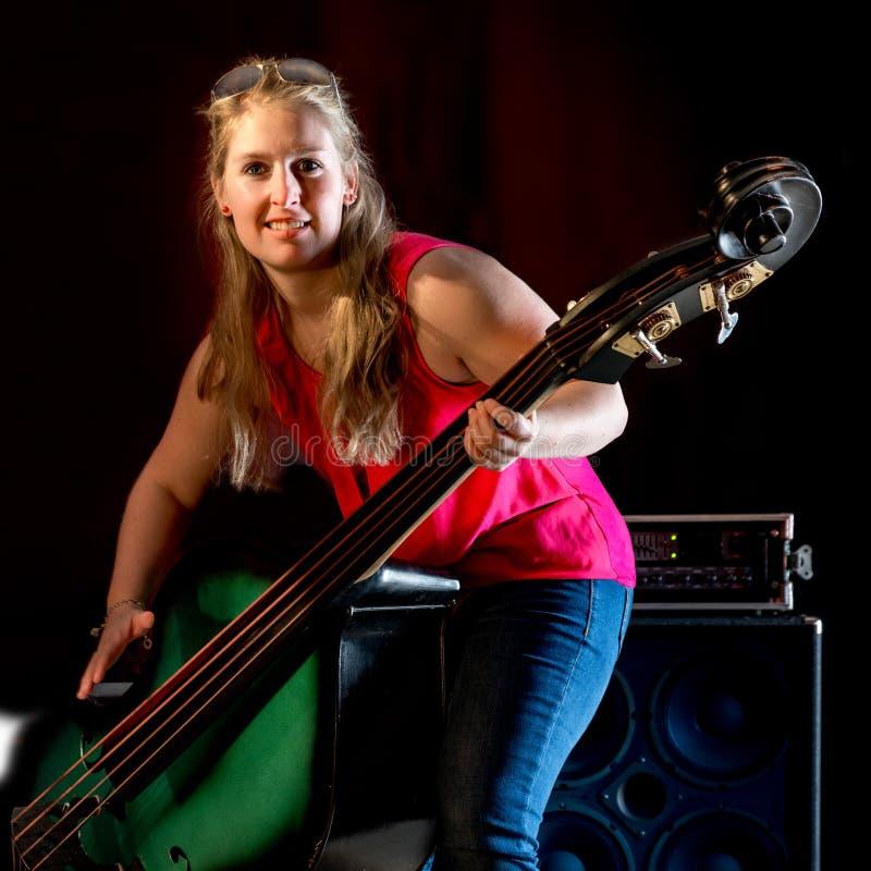 有红色衬衣的女性音乐家在一个低音提琴使用 库存照片