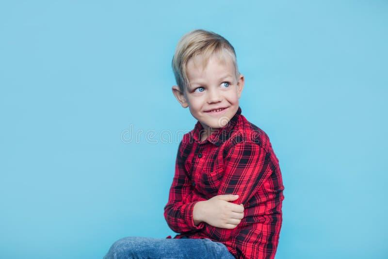 有红色衬衣的时兴的小孩 方式 样式 在蓝色背景的演播室画象 免版税库存图片