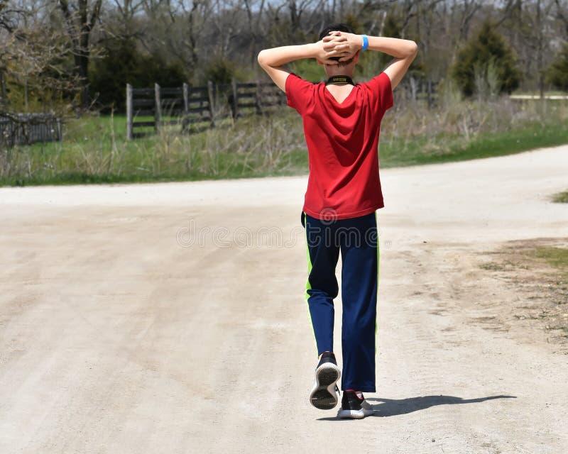 有红色衬衣的男孩步行沿着向下路的 库存照片