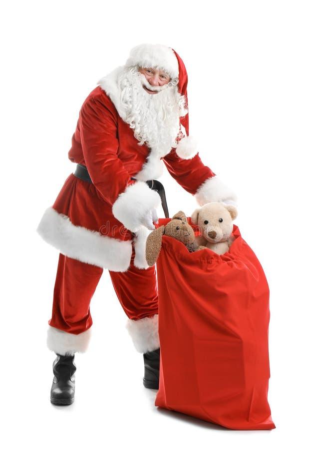 有红色袋子的地道圣诞老人有很多礼物 免版税库存图片