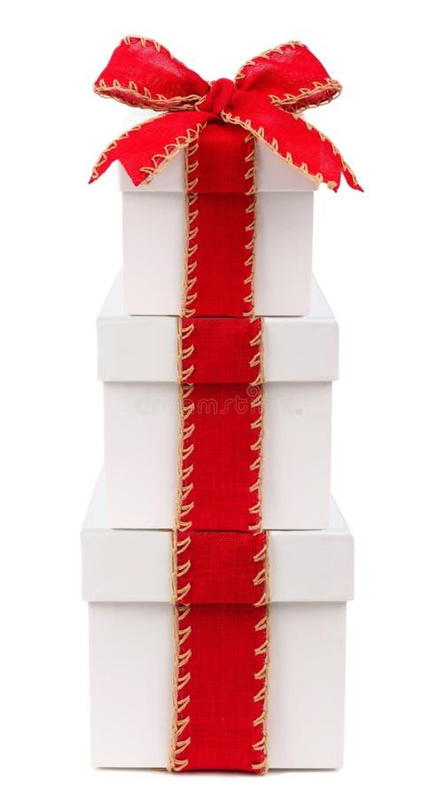 有红色被隔绝的弓和丝带的被堆积的白色圣诞节礼物盒 库存照片