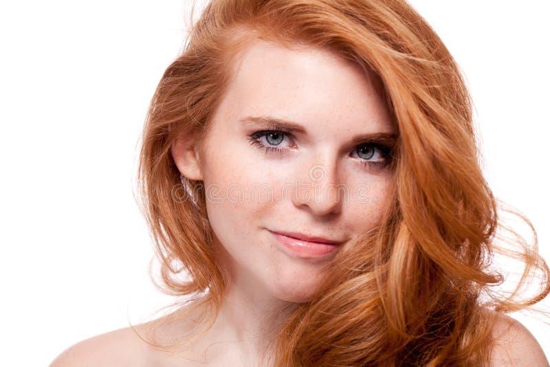 有红色被隔绝的头发和雀斑的美丽的年轻微笑的妇女 库存照片