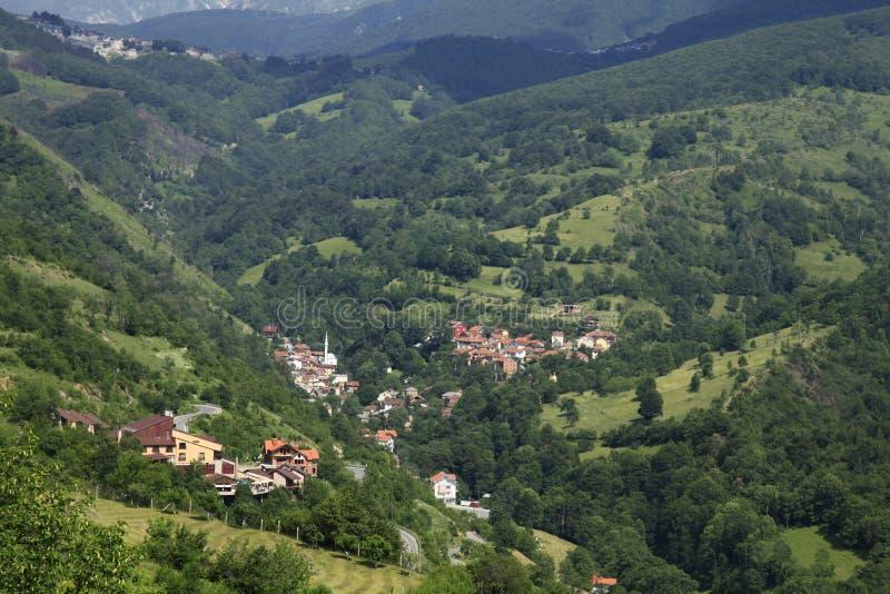 有红色被顶房顶的房子的村庄树木繁茂的山的在科索沃 库存照片