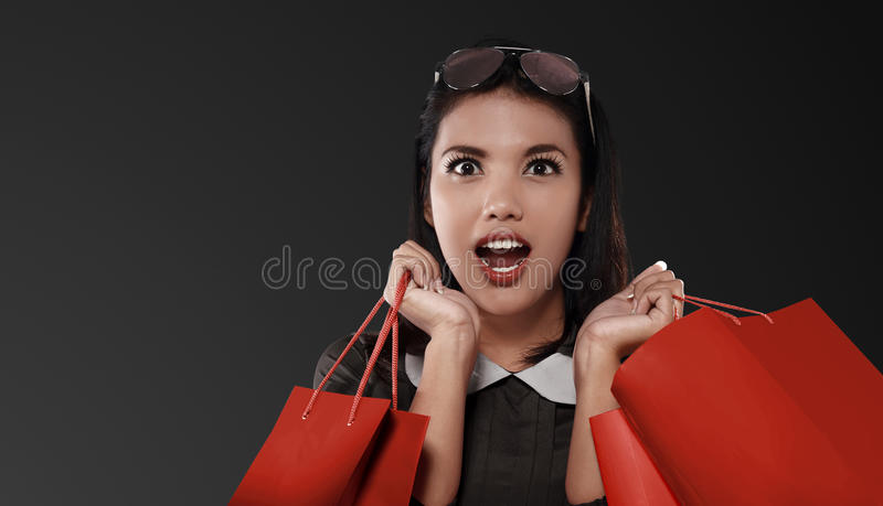 有红色购物袋的愉快的亚裔妇女庆祝黑星期五的 免版税库存图片