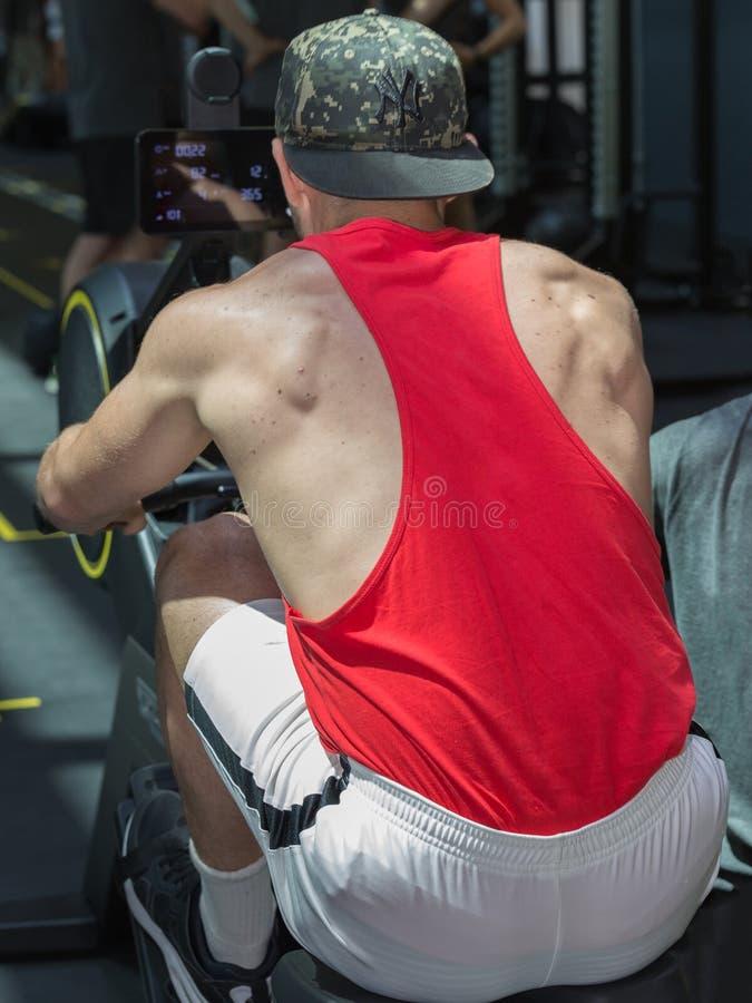 有红色运动服的年轻人行使在划船器的在健身房:健身设备 免版税库存照片