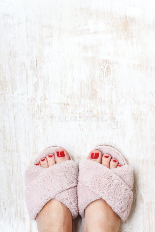 有红色钉子的女性腿在家庭在轻的木背景的毛皮蓬松桃红色拖鞋 r r a的概念 免版税图库摄影