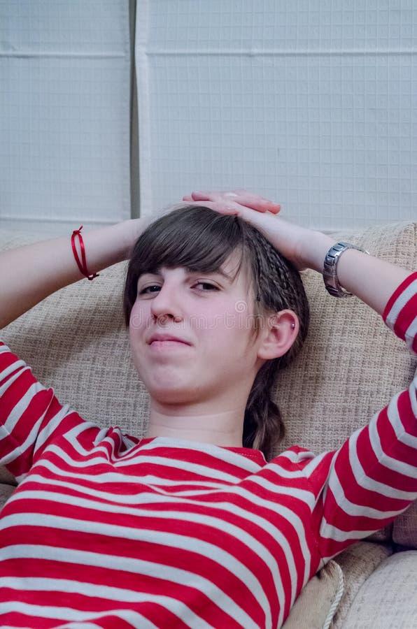 有红色镶边衬衣和胳膊的微笑的年轻女人在头顶上 库存图片