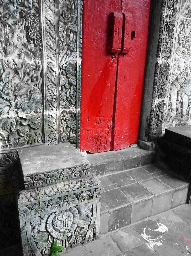 有红色门&石头的巴厘岛房子雕刻了墙壁 免版税库存图片