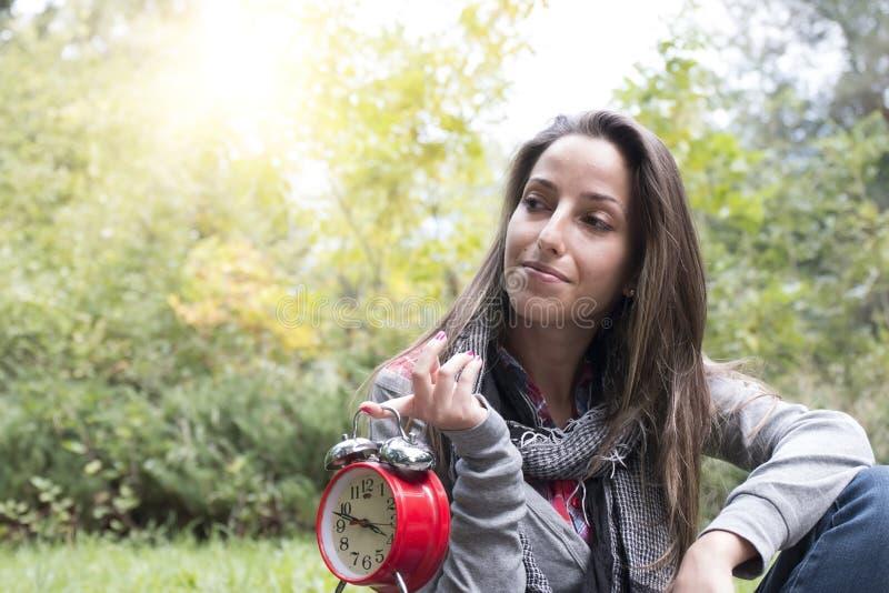 有红色闹钟的少妇在公园 免版税库存照片