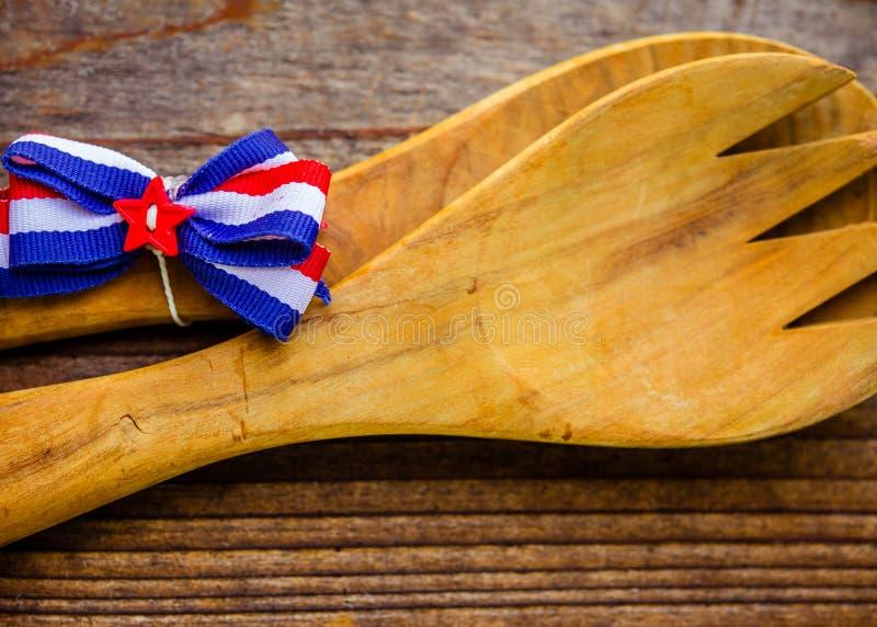 有红色,白色和蓝色弓的大木服务的叉子特写镜头和匙子 免版税库存照片