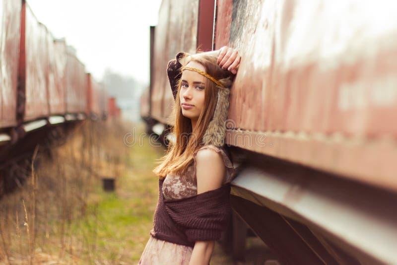 有红色头发和大嘴唇的美丽的嬉皮女孩在老汽车附近站立在铁路附近 图库摄影