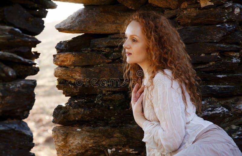 有红色头发和闷热沉思神色的美丽的女孩 免版税库存照片