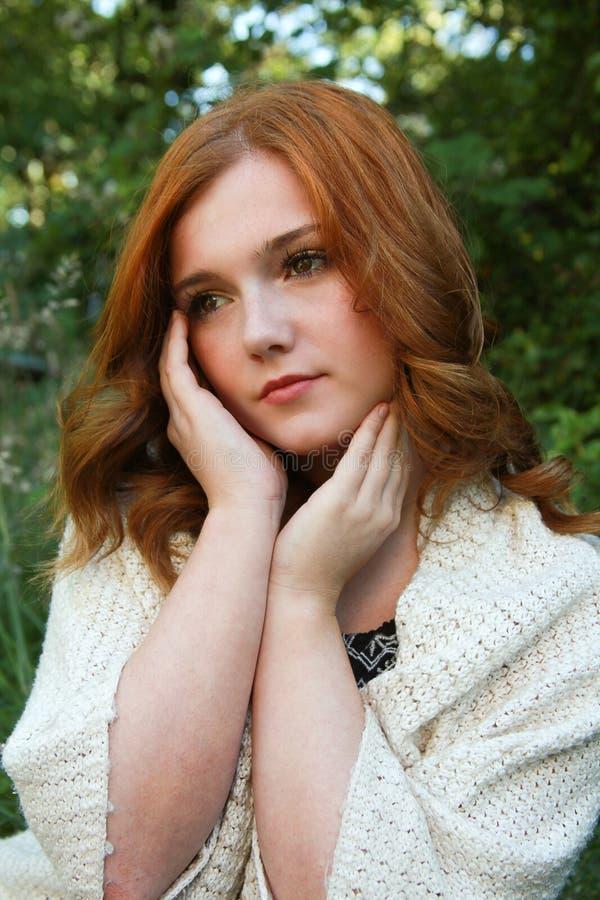 有红色头发天作梦的美丽的少妇 免版税库存图片