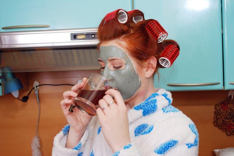 有红色头发有黏土面具的和卷发夹的可爱的女孩在头发在晨衣的厨房里花费并且食用热的茶 免版税图库摄影