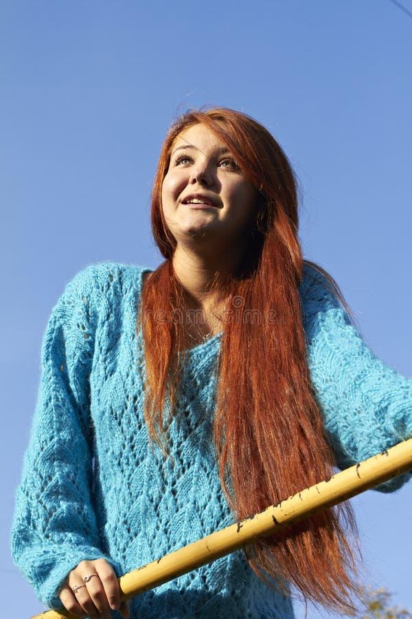 有红色头发的一个年轻美丽的夫人 免版税库存照片