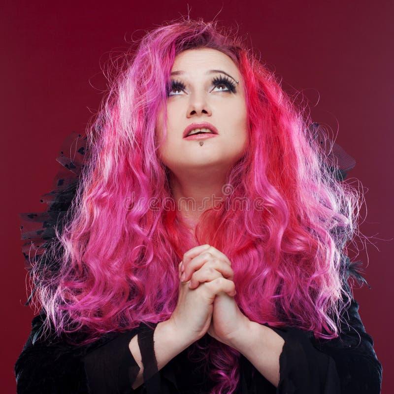 有红色头发的可怕巫婆折叠了她的在祷告的手 美好查找户外妇女年轻人 免版税库存照片