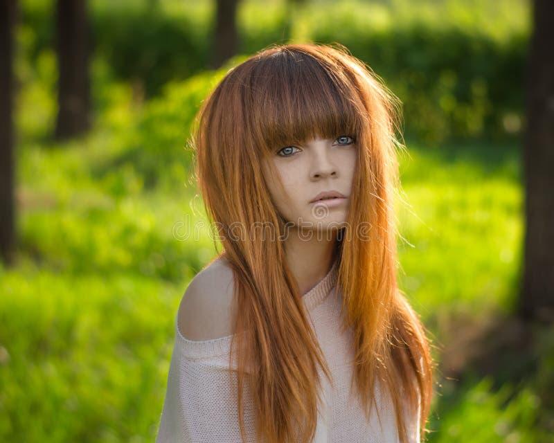 有红色头发的女孩在森林里 免版税库存照片