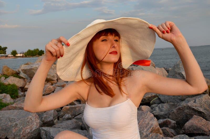 有红色头发的女孩握白色帽子手 库存照片