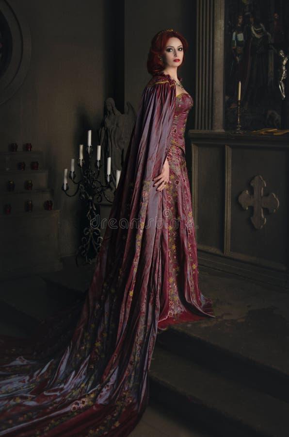 有红色头发的妇女在古老城堡 库存图片
