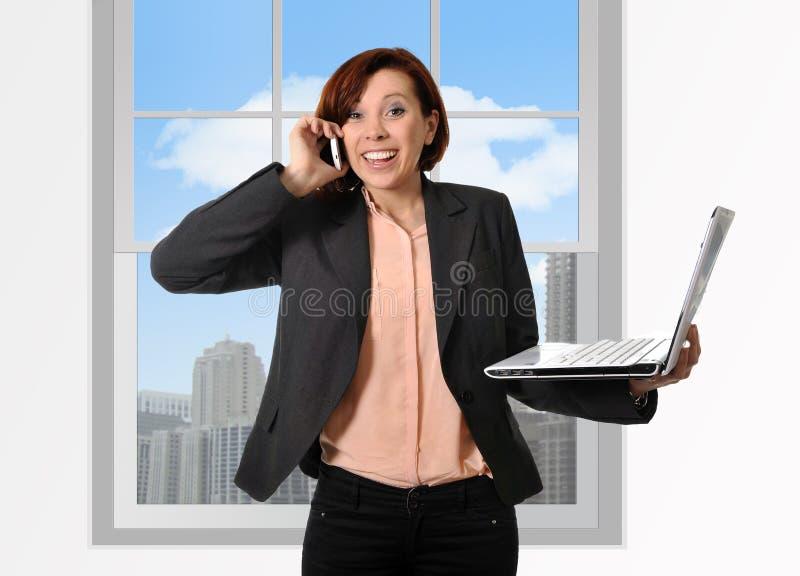 有红色头发的愉快的女商人谈话在举行计算机膝上型计算机手中多任务的流动手机 库存图片