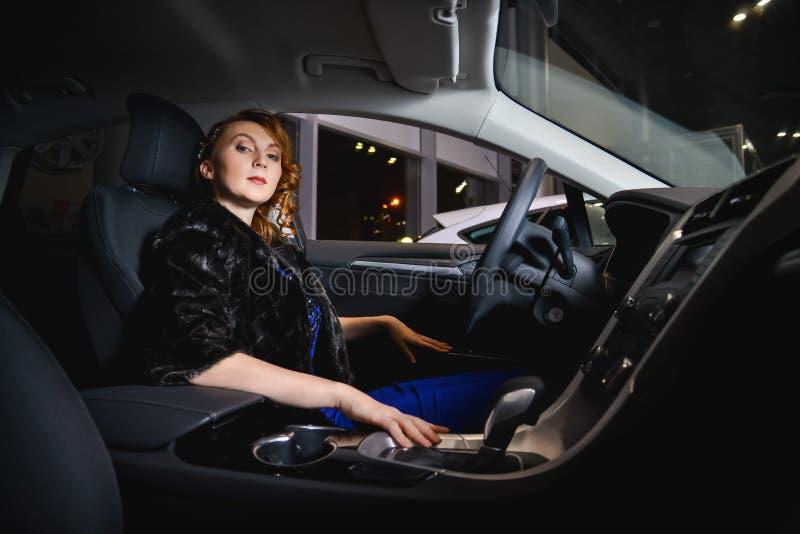 有红色头发的端庄的妇女在长的坐在现代汽车里面的礼服和皮大衣 图库摄影