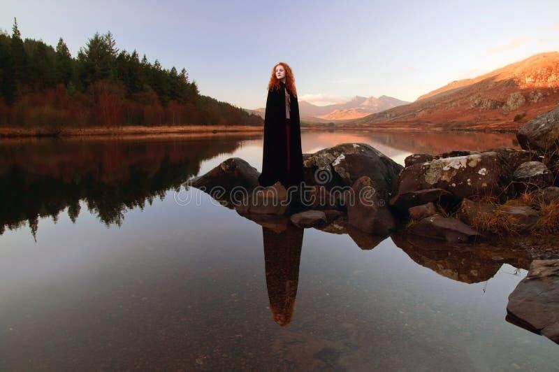 有红色头发的美丽的夫人,穿一个黑斗篷,在湖的寂静的水域中反射了 免版税图库摄影