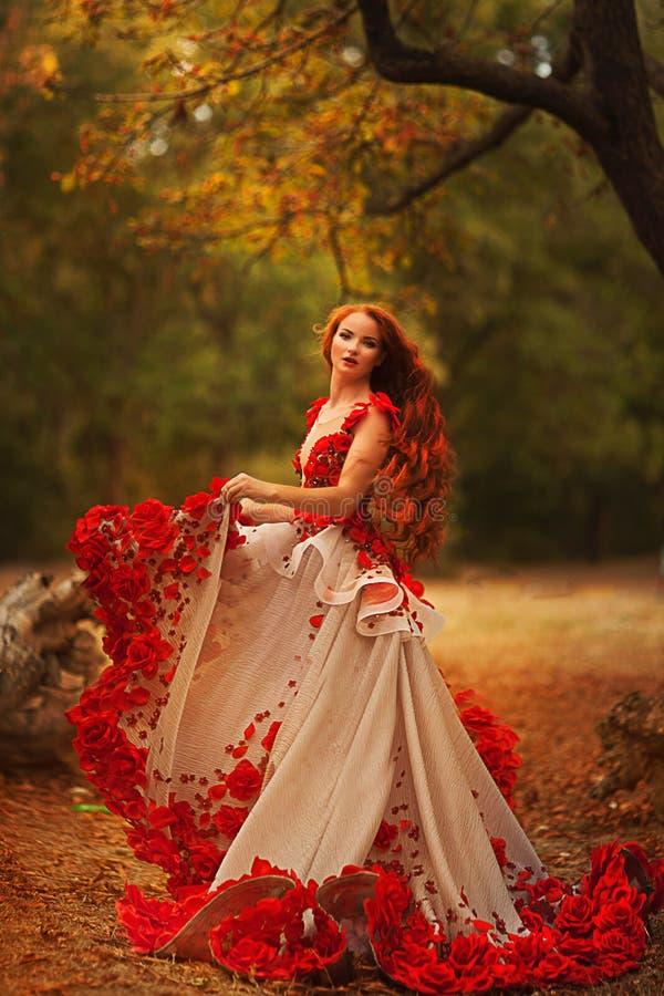 有红色头发的美丽的女孩在秋天公园 免版税库存图片